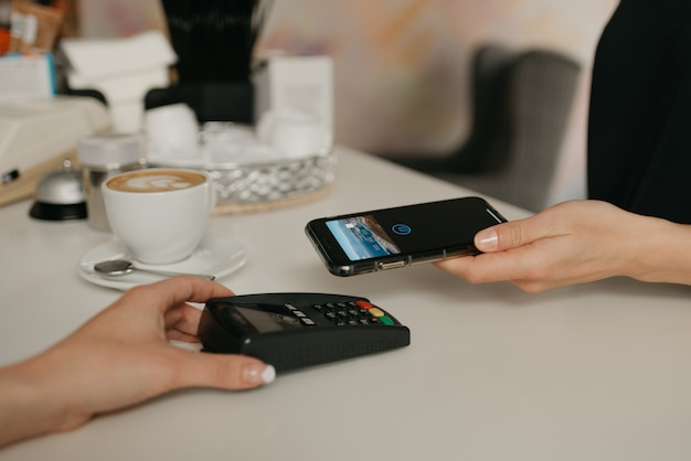 Een meisje betaalt met een smartphone door contactloze nfc-technologie in een café