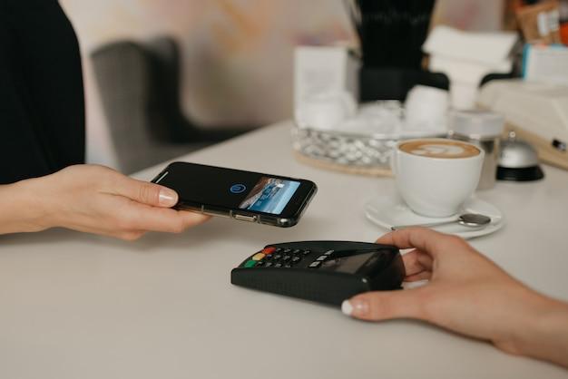 Een meisje betaalt voor haar latte met een smartphone door contactloze nfc-technologie in een café. een vrouwelijke barista houdt een terminal voor het betalen aan een klant in een coffeeshop.