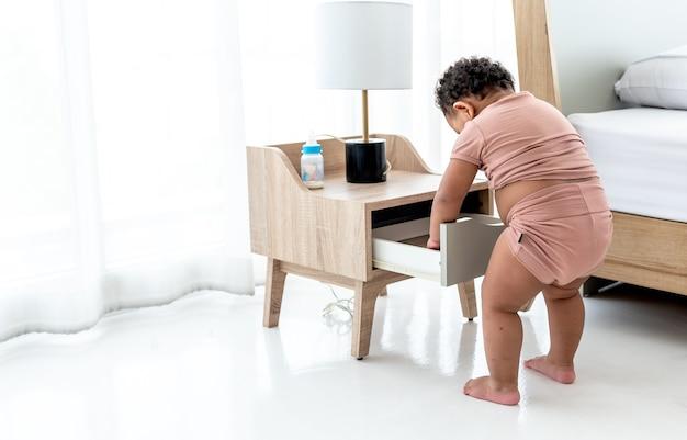 Een meisje dat de lades van het nachtkastje afbreekt, is ondeugend en nieuwsgierig naar de leeftijd en ontwikkeling van het kind