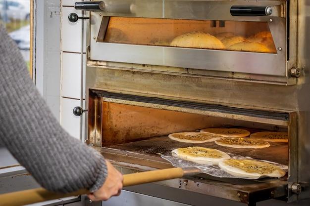 Een meisje dat dönerbroodjes maakt in een lokaal pizza- en gyrosrestaurant