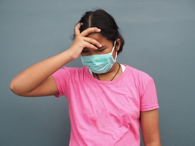 Een meisje dat een beschermend masker draagt met zijn hand op de slapen wegens ziek zijn.