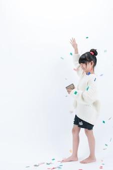 Een meisje dat een brei over een witte achtergrond draagt viert met gekleurd papier in de lucht.