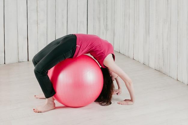 Een meisje dat een brug maakt over een roze fitball in een sportschool