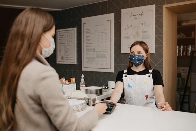 Een meisje dat een medisch gezichtsmasker draagt, gebruikt een smartphone om met nfc-technologie te betalen. een vrouwelijke barista in een gezichtsmasker houdt een terminal voor contactloos betalen aan een klant.