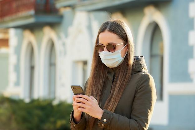 Een meisje dat een smartphone gebruikt, draagt een medisch gezichtsmasker om de verspreiding van het coronavirus in een stadsstraat te voorkomen