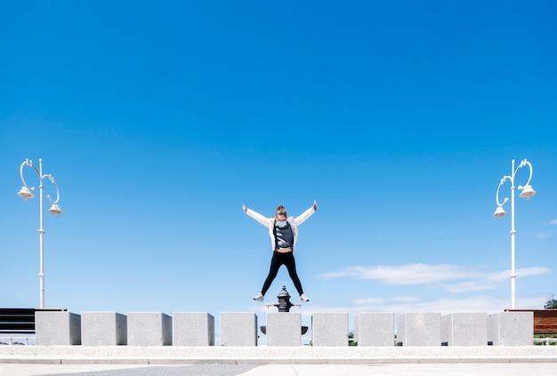 Een meisje dat een veiligheidsmasker draagt, heeft plezier bij het springen door een betonnen muur van een wandeling met straatverlichting in de stad met blauwe lucht op een zonnige dag