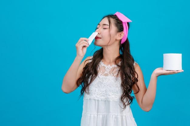 : een meisje dat een witte pyjama draagt die een tissue snuift en een tissue in haar hand houdt op een blauwe.