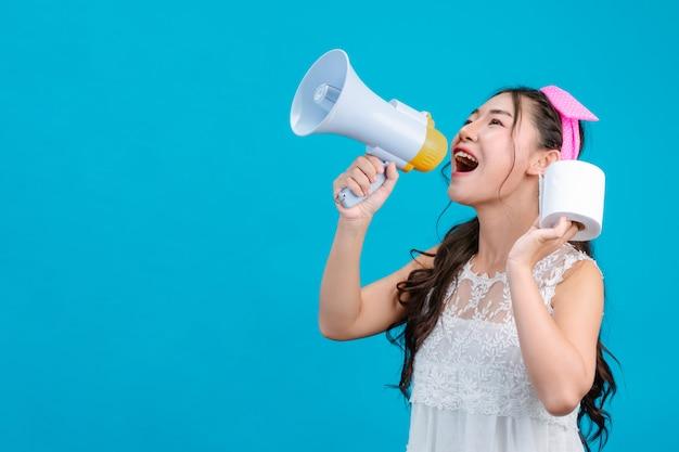 : een meisje dat een witte pyjama draagt, een megafoon vasthoudt en tissuepapier in haar hand houdt op een blauwe.