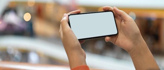 Een meisje dat horizontale smartphone houdt terwijl status bij balkon in winkelcomplex