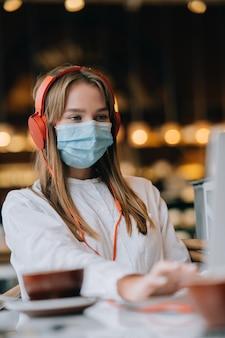 Een meisje dat in een coffeeshop zit met een uitbraak van het coronavirus
