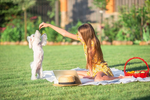 Een meisje dat met haar puppy aan het picknicken is in het park
