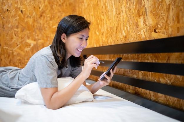 Een meisje dat op een witte matras slaapt en met een mobiele telefoon speelt