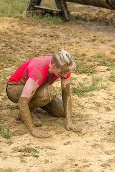 Een meisje dat op haar knie staat en vuil van haar handen op de grond veegt nadat ze door het obstakel is gegaan.