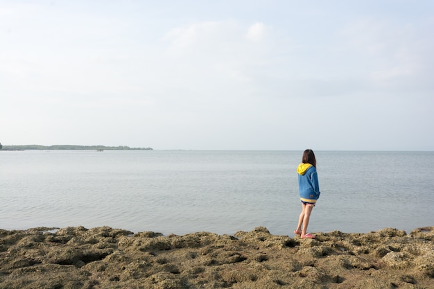 Een meisje dat op het strand achteruitgaat