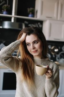 Een meisje dat 's ochtends thuis koffie drinkt in de keuken