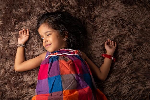 Een meisje dat verschillende uitdrukkingen laat zien en op een synthetisch tapijt ligt