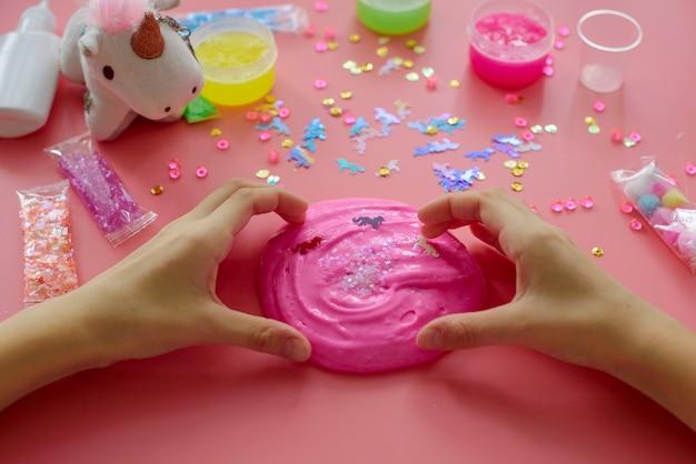 Een meisje dat zelf slijm maakt. kind dat slijm op roze achtergrond maakt.