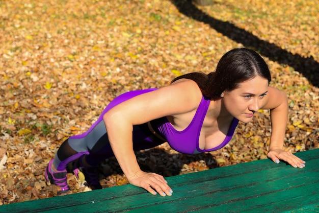 Een meisje doet push-ups vanaf een bankje in het park. sporten in de open lucht