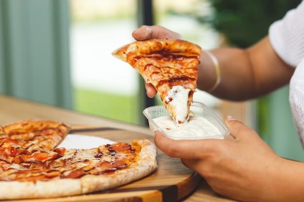 Een meisje doopt een stuk pizza in saus in een plastic bakje voordat ze het eet