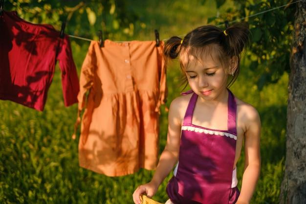Een meisje draagt natte kleren na het wassen om aan een waslijn te drogen