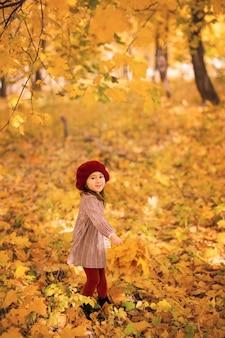 Een meisje draait op een herfstdag in het park met een boeket esdoornbladeren