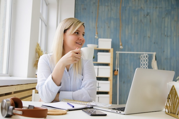 Een meisje drinkt koffie aan haar bureau
