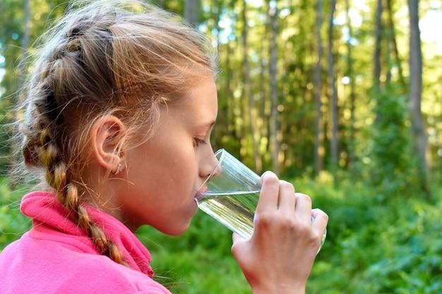 Een meisje drinkt schoon water uit een glas