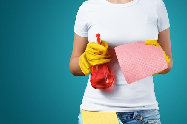 Een meisje een schoonmaakster met een reinigingsmiddel die handschoenen en een vod op een blauwe achtergrond draagt