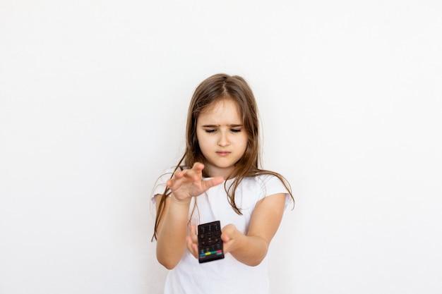 Een meisje, een tiener met een afstandsbediening van de tv, schakelt tussen kanalen, zoekt naar een tekenfilm, is niet gelukkig, kijkverbod, kinderen en volwassenen, tv en internet, entertainment