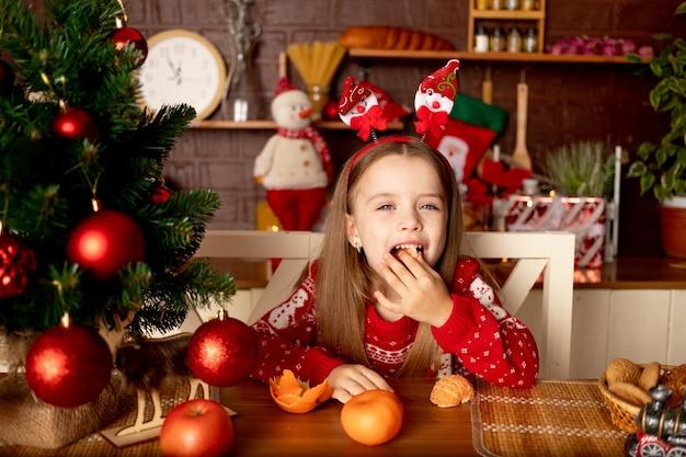 Een meisje eet mandarijnen in een donkere keuken bij een kerstboom met rode ballen verheugt zich en glimlacht, het concept van nieuwjaar en kerstmis