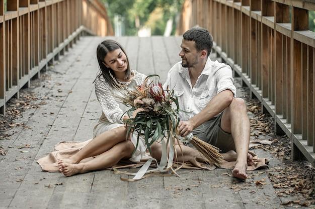 Een meisje en een jonge man zitten op de brug en genieten van communicatie, een date in de natuur, een liefdesverhaal.