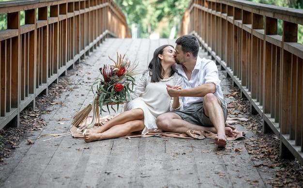 Een meisje en een jonge man zitten op de brug en kussen, een date in de natuur, een liefdesverhaal.