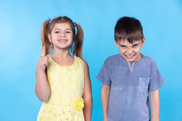 Een meisje en een jongen een meisje zegt tegen een jongen dat hij een lesje moet leren een jongen wil niet hij is boos een meisje draagt een jurk een jongen draagt een shirt blauwe achtergrond