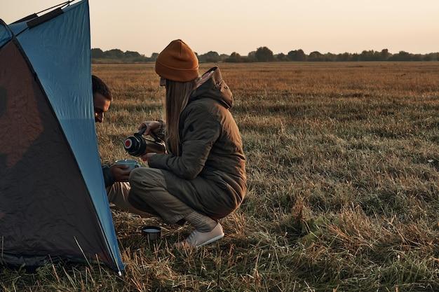 Een meisje en een jongen in een tent drinken uit een mok, herfsttijd, reizen. ze ontmoeten de dageraad in de natuur.