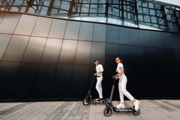 Een meisje en een jongen lopen op elektrische scooters door de stad
