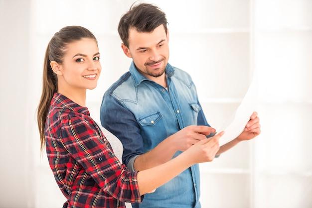 Een meisje en een man overwegen een plan voor een nieuw appartement.