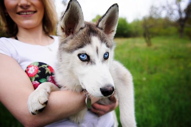 Een meisje en haar hond husky wandelen in een park