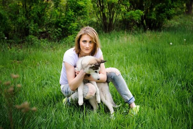 Een meisje en haar hond husky wandelen in een park.