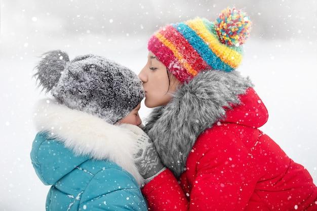 Een meisje en haar zus wandelen in een winterpark met een hond