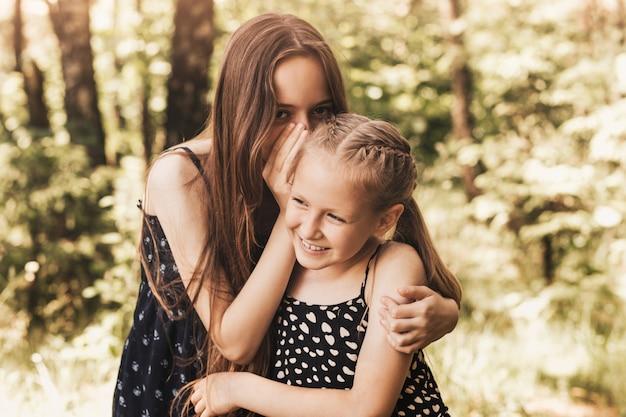 Een meisje fluistert een geheim in het oor van haar zus