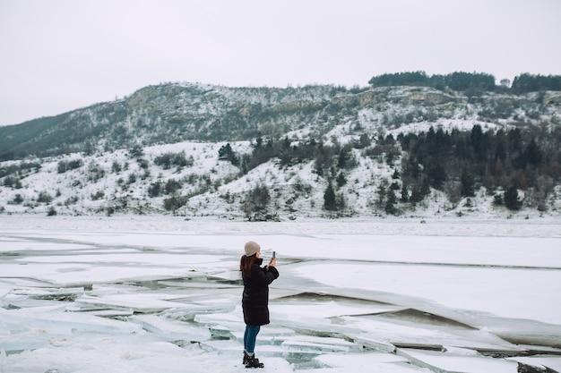 Een meisje fotografeert aan de telefoon een bevroren meer met grote ijsschotsen.