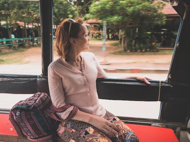 Een meisje gaat op een olifantenboerderijtour achter in een taxitruck op het eiland koh chang, thailand