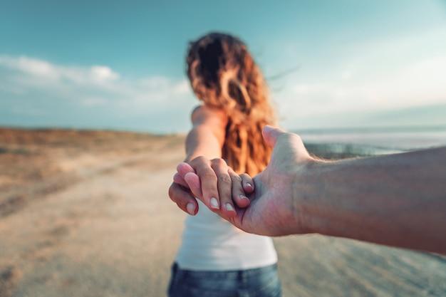 Een meisje gaat op een post met een kerel aan een hand