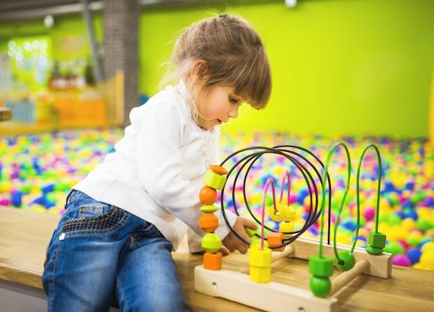 Een meisje gekleed in een spijkerbroek en een witte trui speelt met een zich ontwikkelend houten speelgoed in de speelkamer.