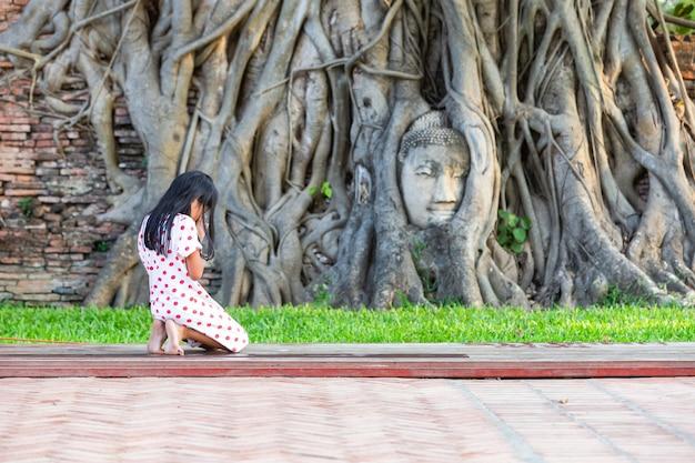 Een meisje geknield bidden voor heilig aan het hoofd van boeddhabeeld in de boomwortels van wat mahathat in de provincie ayutthaya, thailand
