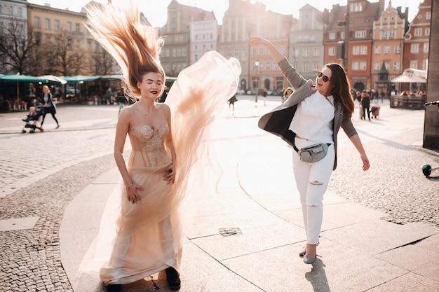Een meisje gooit een trouwjurk naar een bruid met lang haar in de oude binnenstad van wroclaw. bruiloft fotoshoot in het centrum van een oude stad in poland.wroclaw, polen.