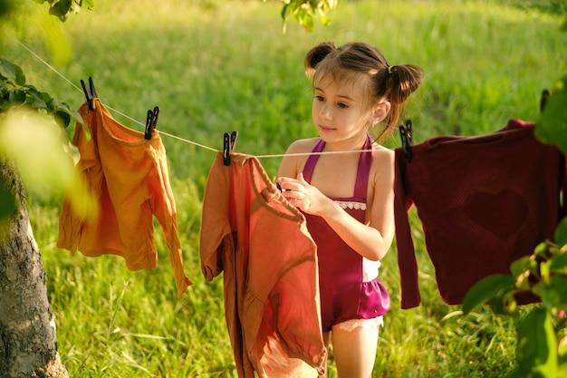 Een meisje hangt een gewassen jurk te drogen aan een waslijn in de tuin onder een boom
