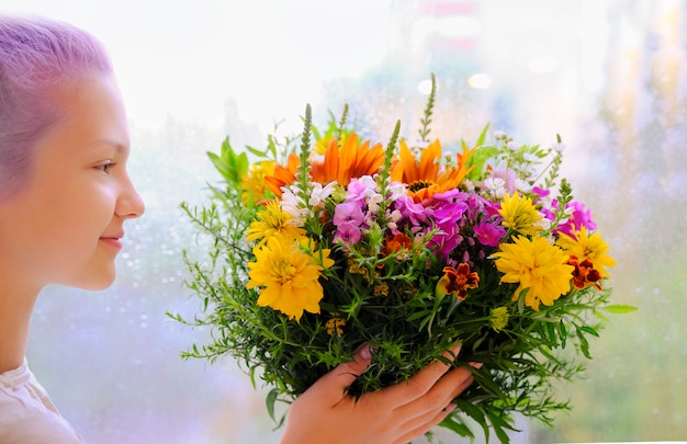Een meisje heeft een boeket wilde bloemen in haar handen. kort kapsel. lila haar.