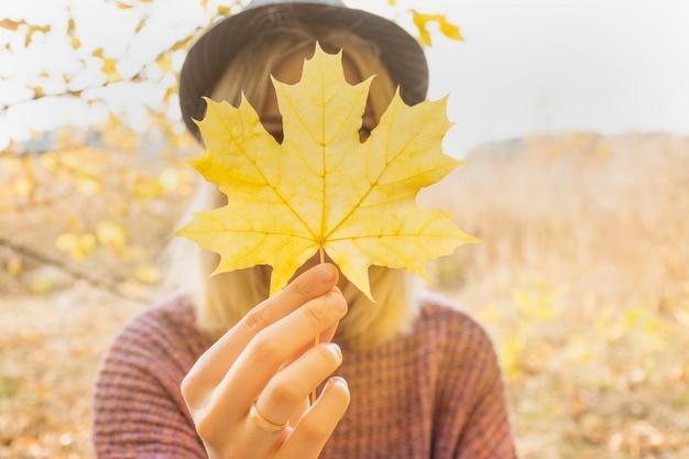 Een meisje heeft een esdoornblad in haar hand. warme herfstdag, gele herfstbladeren. herfst concept.