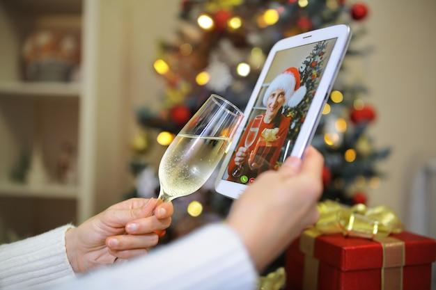 Een meisje heft het glas op haar metgezel die in de kerstboom met haar aan de telefoon staat